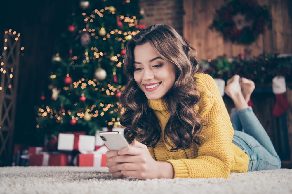 Femeie cu pulover galben, așezată lângă brad, ține telefonul în mână și zâmbește citind mesaje de Crăciun