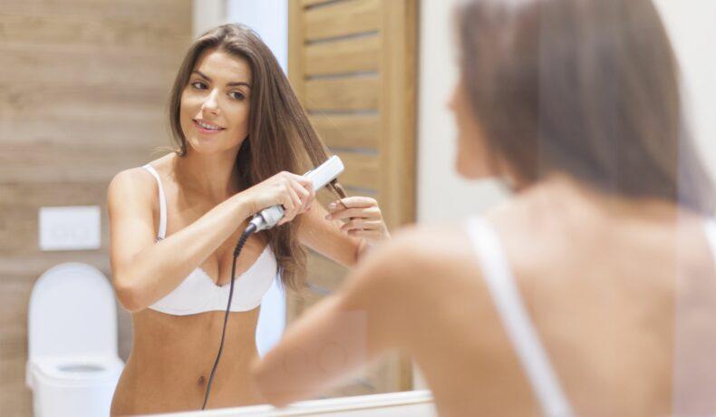 O femeie se coafează cu ajutorul unei plăci de îndreptat părul.