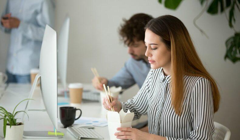 O femeie care mănâncă repede în timp ce stră la birou, în fața unui calculator.