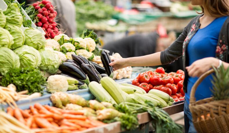 O femeie care alege legume la piață