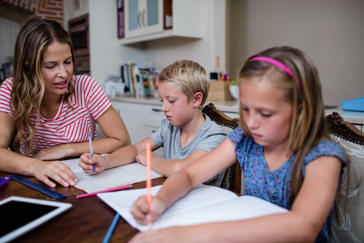 Mamă care stă la masă cu copiii și îi ajută la teme