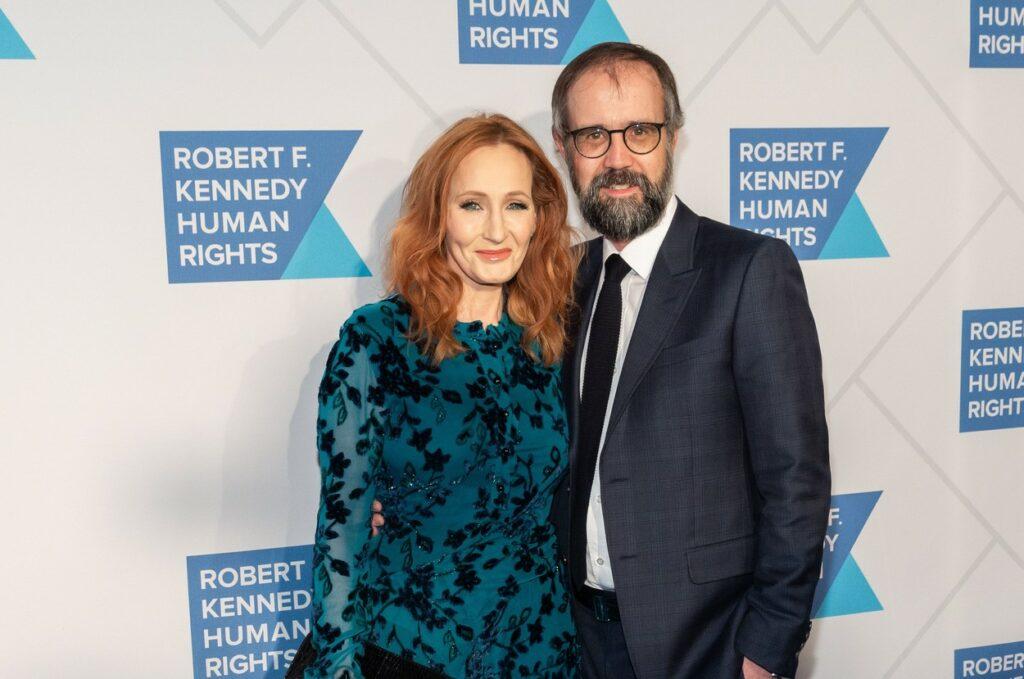 J. K. Rowling pozează pe covorul roșu alături de soțul ei. Ea poartă o rochie albastră și el un costum albastru