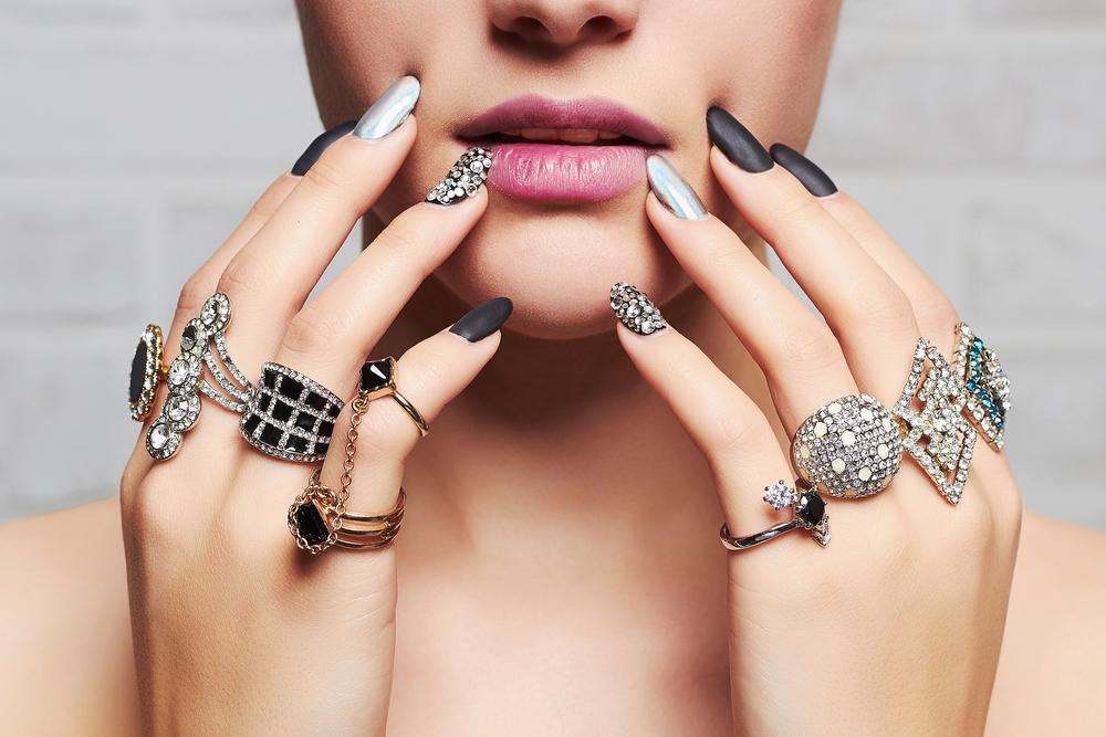 O femeie care poartă o mulțime de inele pe fiecare deget