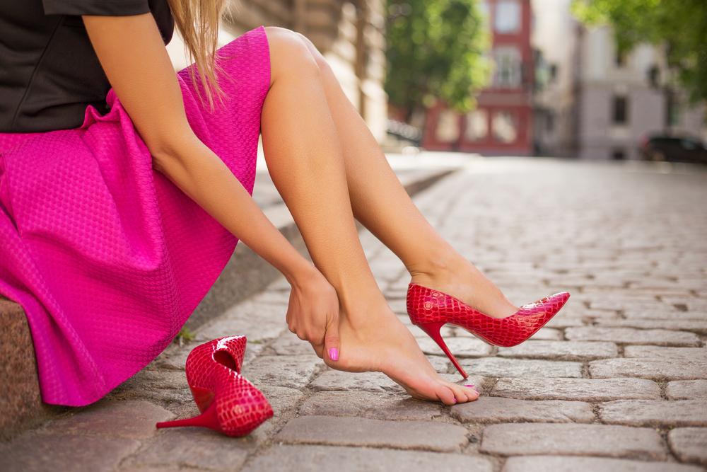 O femeie care stă pe bordură din cauza durerii de picioare cauzate de pantofii cu toc