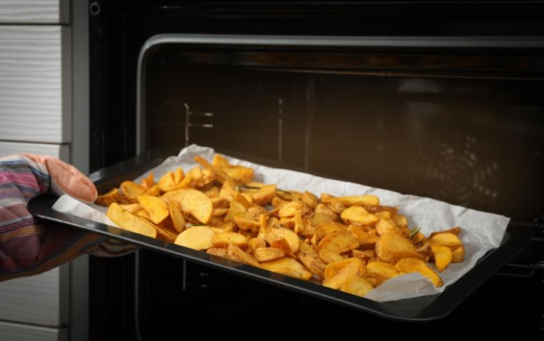 O tavă cu plină cu cartofi tăiați, pregătiți pentru cuptor pentru a obține cei mai crocanți cartofi la cuptor
