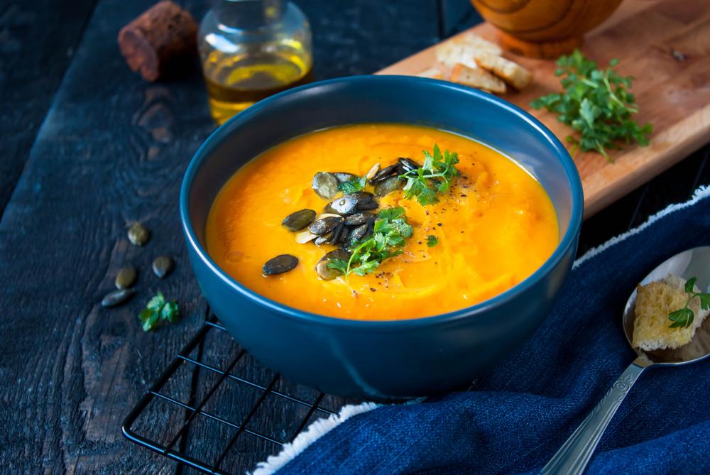 Supă cremă de dovleac într-un recipient din ceramică