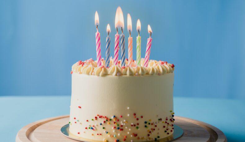 Tort cu cremă albă, decorat cu bomboane multicolore și lumânări pentru a sărbători o zi de naștere.
