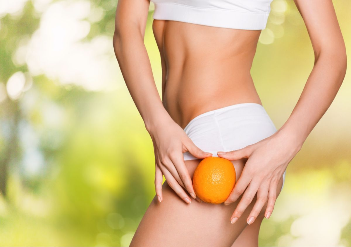 Parte din corpul unei femei, îmbrăcată în lenjerie intimă. Femeia ține o portocală pe coapsă pentru a evidenția un loc posibil de apariție a celulitei.