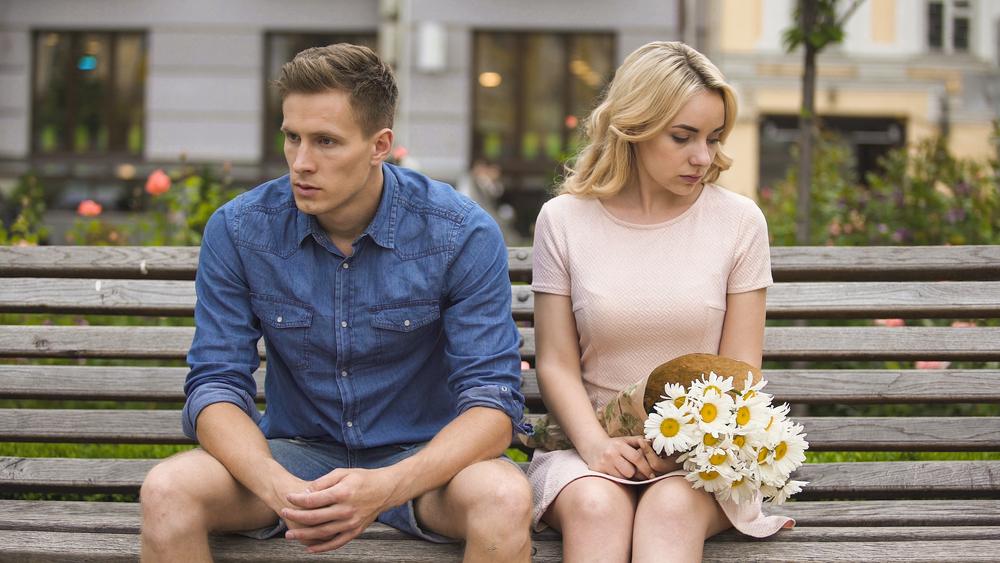 Un bărbat și o femeie cu fețe triste stau pe o bancă și privesc în direcții diferite