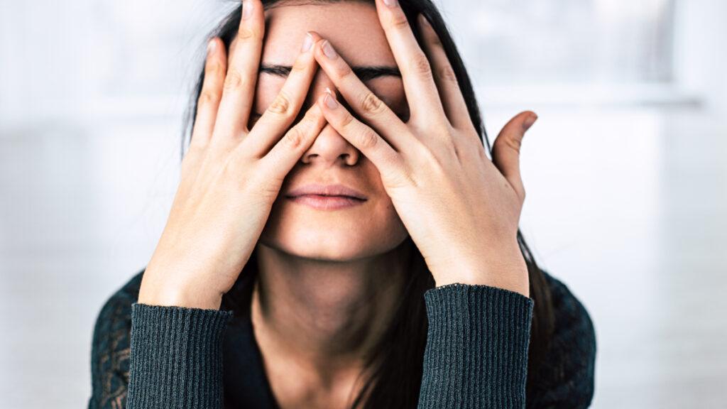 O femeie își acoperă fața cu palmele