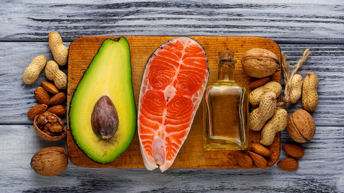 Jumătate de avocado, un file de somon, nuci și ulei sunt așezate pe un platou de lemn