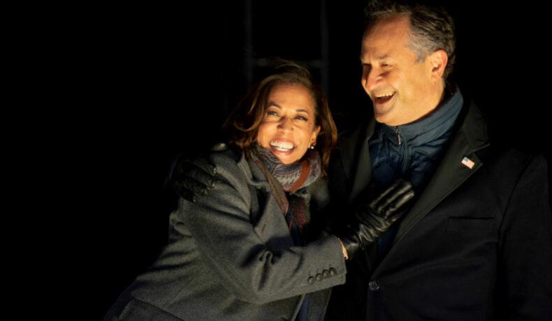 Kamala Harris îl îmbrățișează pe Doug Emhoff în timp ce afișează un zîmbet larg