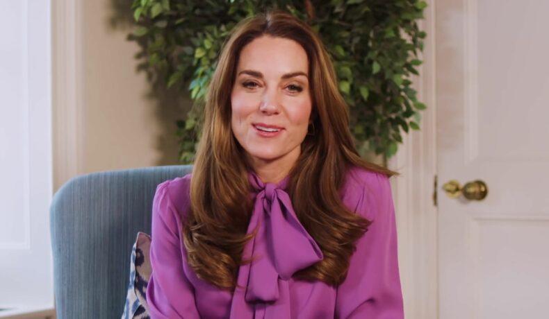 Kate Middleton stă pe un fotoliu albastru îmrăcată cu o cămașă lila cu fundă la gât