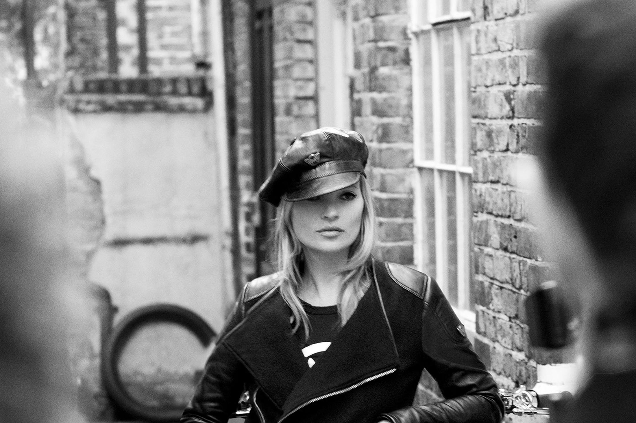 Fotografie alb-negru cu Kate Moss în care modelul poartă o șapcă elegantă și o geacă neagră de piele