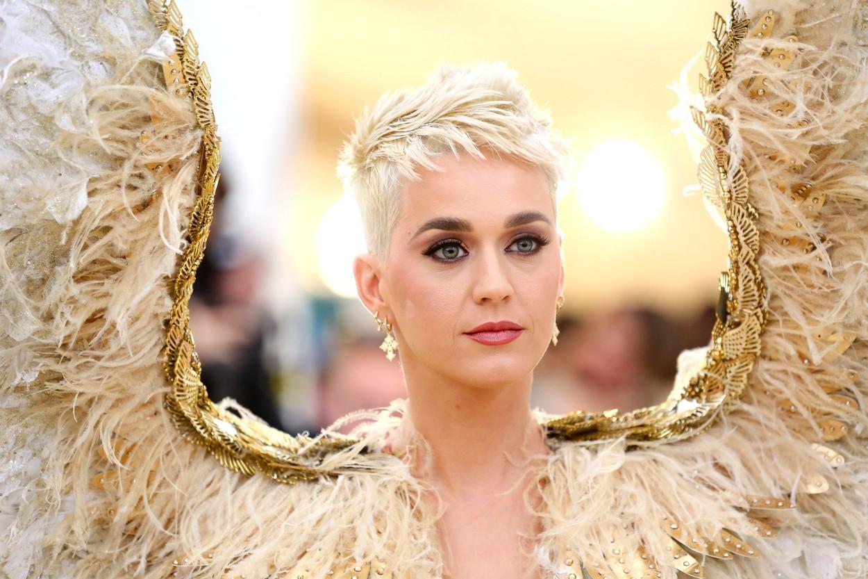 Portret cu Katty Perry e covorul roșu machiată cu fard negru. Are părul scurt ș blond și poartă o pereche de aripi