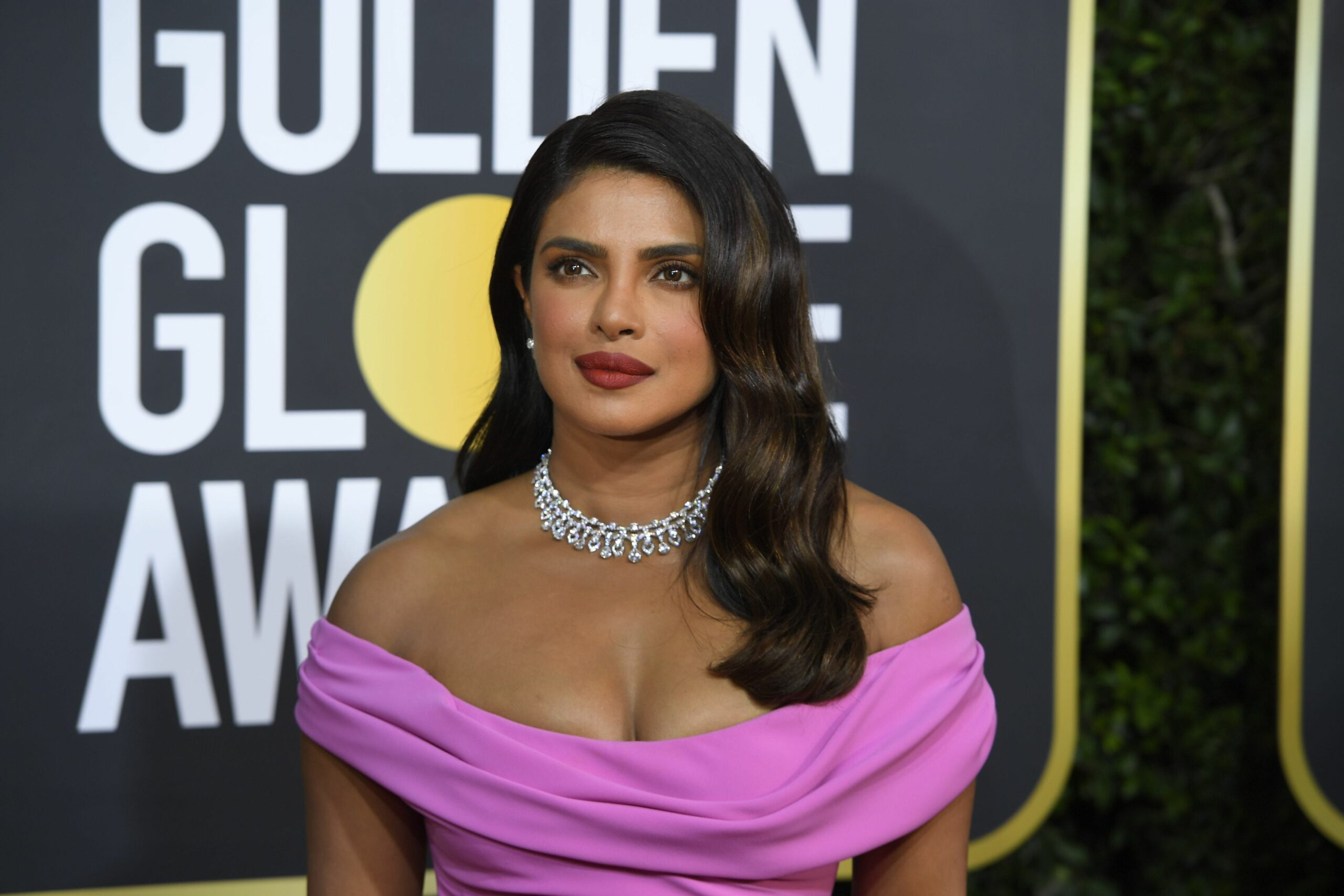 Priyanka Chopra îmbrăcată într- rochie mov cu umerii dezgoliți și un colier pe covorul rosu de la Golden Globe Awards