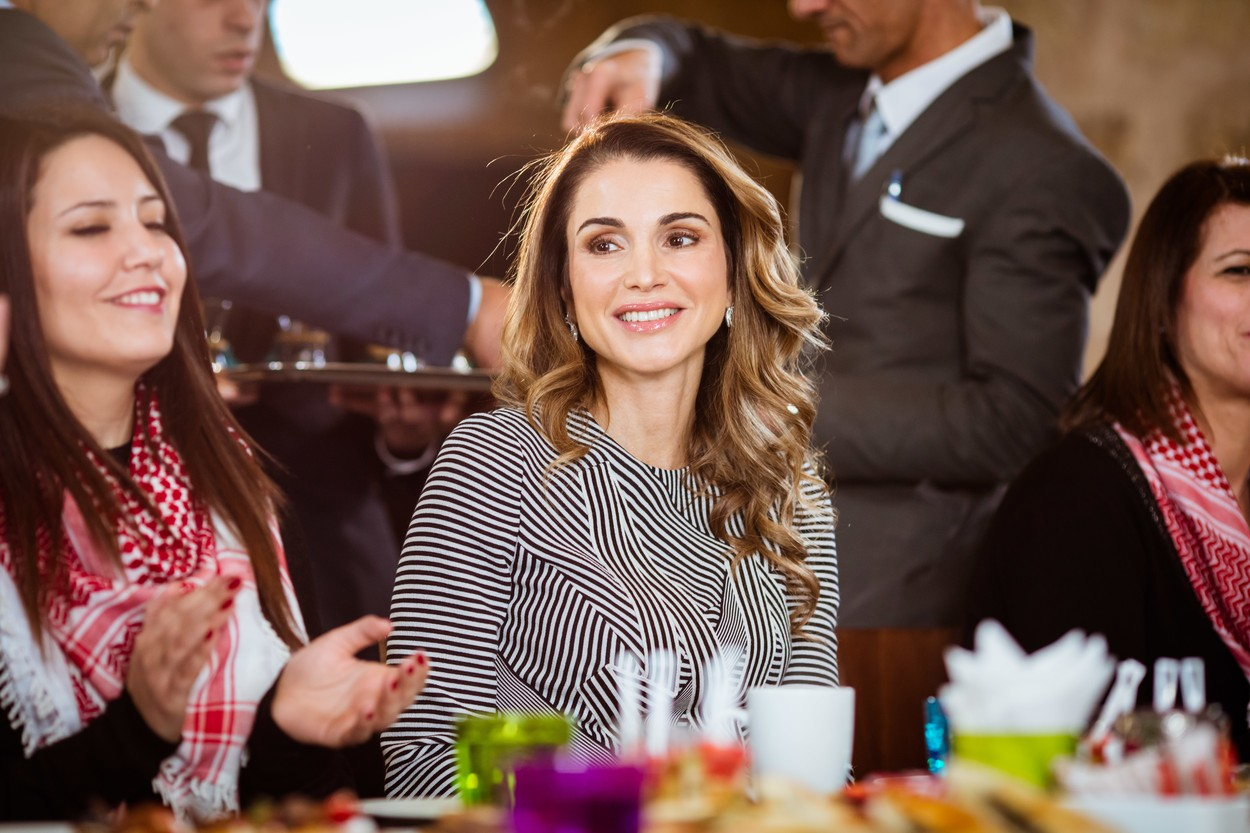 Regina Rania zâmbește larg în timpul unei întâlniri. Poartă o bză gri și părul lung și ondulat îi atârnă pe umeri