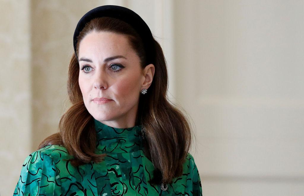 Kate Middleton îmrăcată într-o rochie verde, porată o coroniță neagră pe cap și este fardată cu machiaj negru