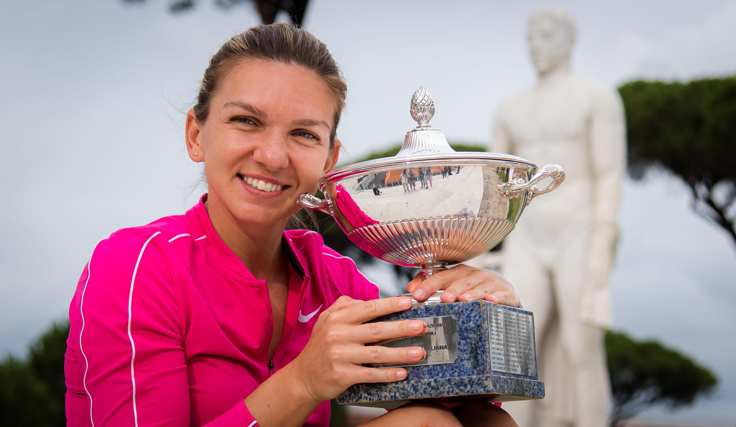 Simona Halep zâmbește și ține în mână un trofeu argintiu. Este îmbrăcată într-o bluză sport roz