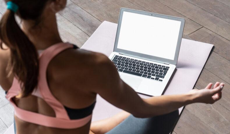 O femeie îmbrăcată cu o bustieră sport și colanți stă într-o poziție de yoga în fața unui laptop