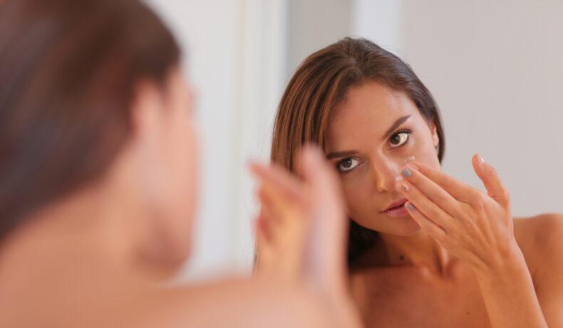 O femeie cu păru lung castaniu se uită în oglindă în timp ce își curăță tenul