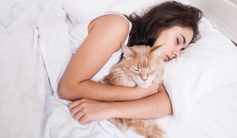 O femeie cu părul lung șaten dare cu o pisică portocalie în brațe pe așternuturi albe
