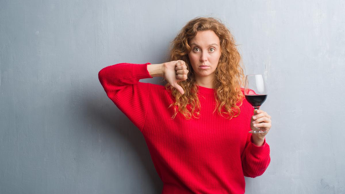 O femeie cu părul creț și blond îmbrăcată într-un pulover roșu ține în mână un pahar de vin roșu, iar cu cealaltă mână arată semnul dislike
