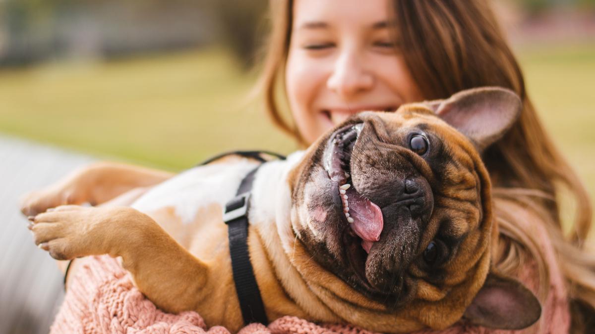 O femeie care zâmbește larg ține în brațe un câine maro care scoate limba afară