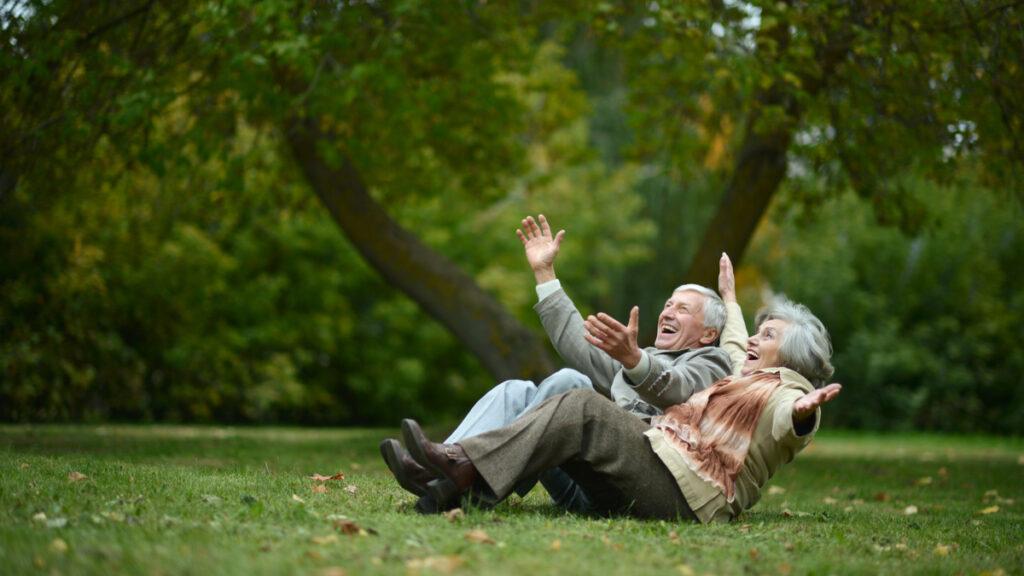 O femeie și un bărbat în vârstă stau întinși pe oarbă în parc și zâmbesc în timp ce țin mâinile în sus