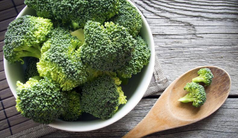 Imagine cu un bol de broccoli verde și o lingură de lemn alături