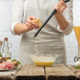 Un chef dă pe răzătoare o bucată de parmezan, deasupra unui bol în care se află ouă bătute.