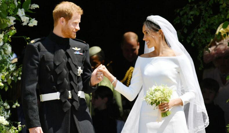 Meghan Markle îmbrăcată în rchie de mireasă îl ține de mână pe prințul harry