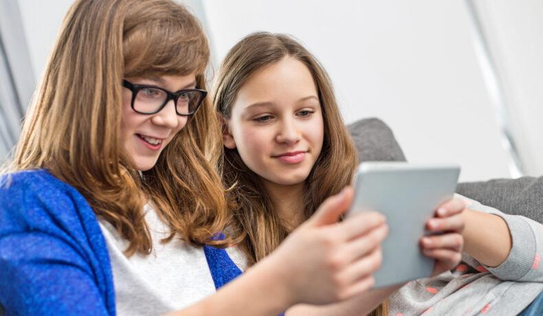 Două fete stau pe canapea și se uită pe o tabletă