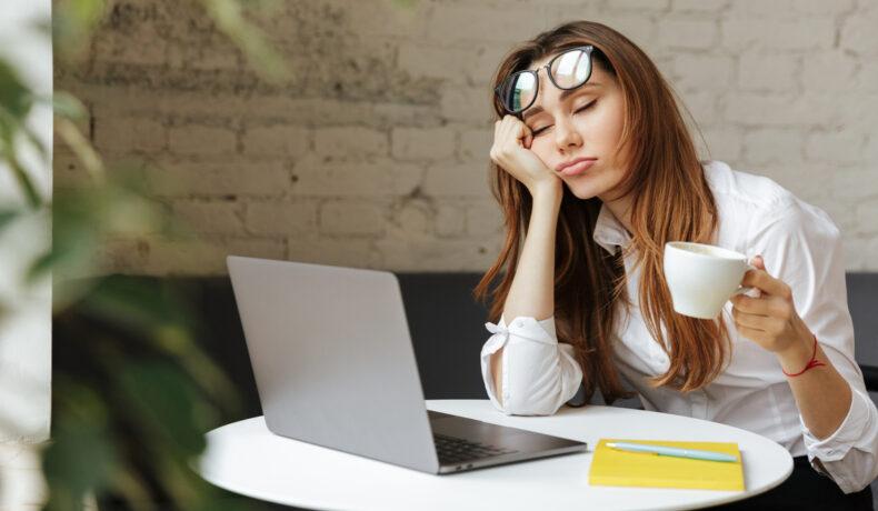 O fată tănără ăși srpijină capul pe mână și ține o cană de cafea în cealaltă mână. Stă la o masă pe carese află un laptop