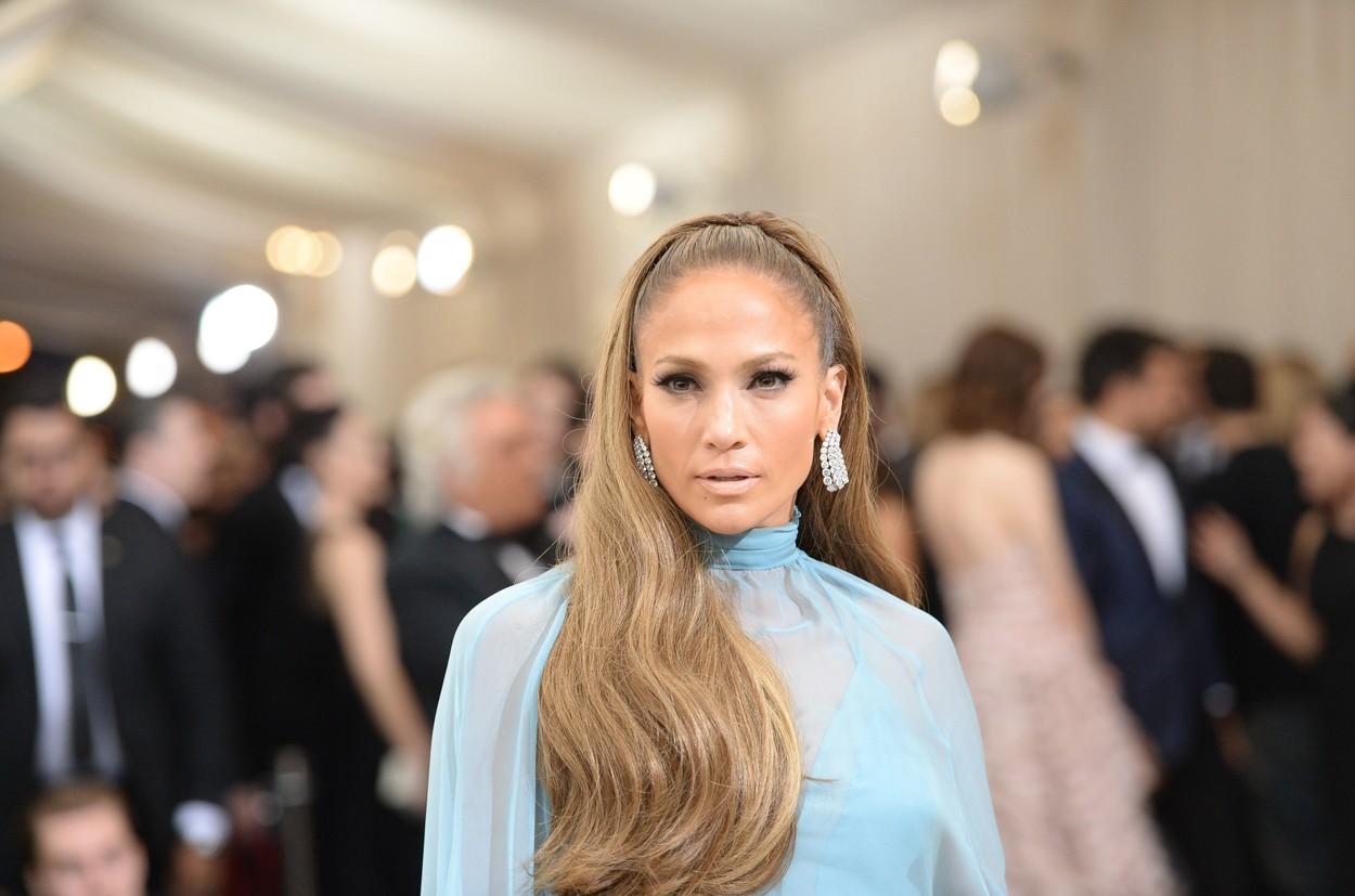 Jennifer Lopez poartă o rochie albastru deschis și are părul prins într-o coadă elegantă