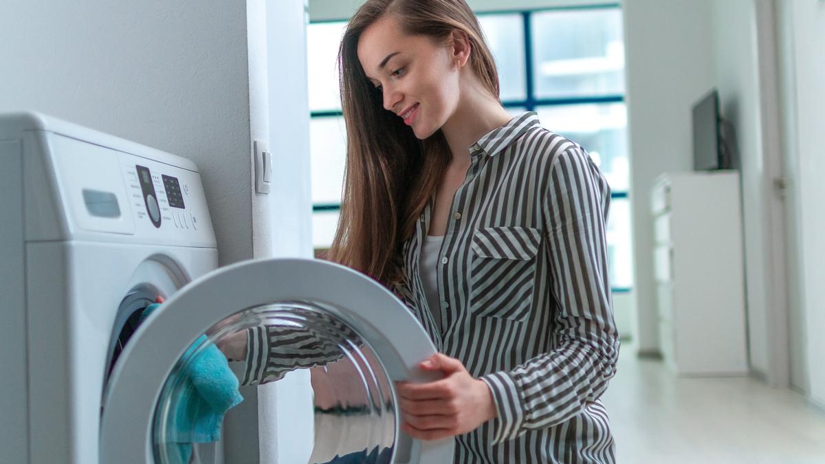 O fată tânrără cu păru lung și îmbrcată cu o cămașa cu dungi albe și negre crăță mașina de spălat cu un prosop albastru