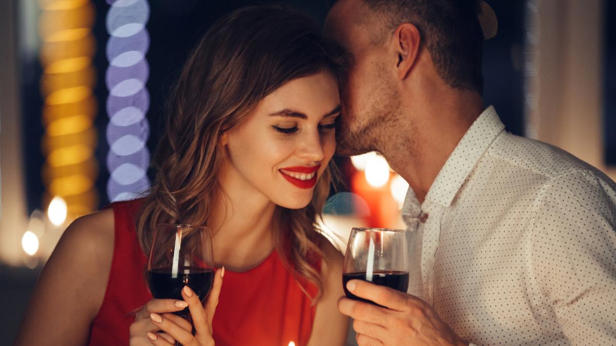 Un bărbat sărută o femeie atrăgătoare pe obraz în timpl unei cine. Amândoi țin în mână un pahar de vin