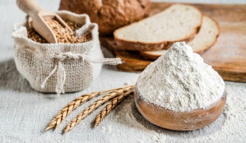 Bol de făină albă, câteva spice de grâu. Pe fundal se observă o pâine albă, feliată, obținută din făină albă.