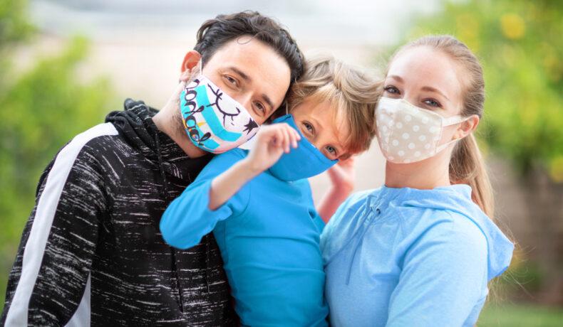 O femeie, un bărbat și un copil care formează o familie se îmbrățișează și poartă măști de protecție din material textil