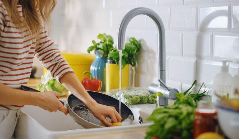 O femeie care spală o tigaie încinsă la chiuvetă
