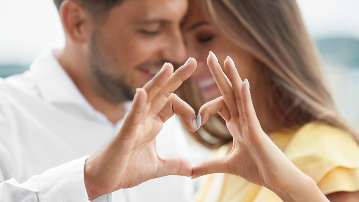 Un bărbat și o femeie se îmbrățișează și își țin mâinile în forma unei inimi
