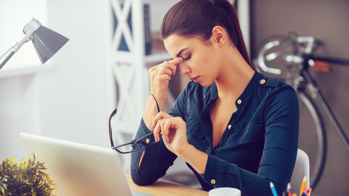 O femeie stă la birou șși își masează fruntea