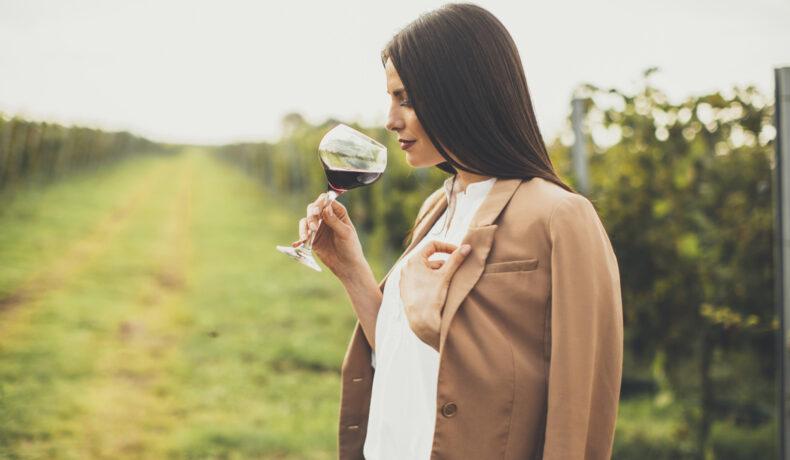 O femeie cu părul lung șaten bea un pahar de vin roșu pe o plantație de struguri