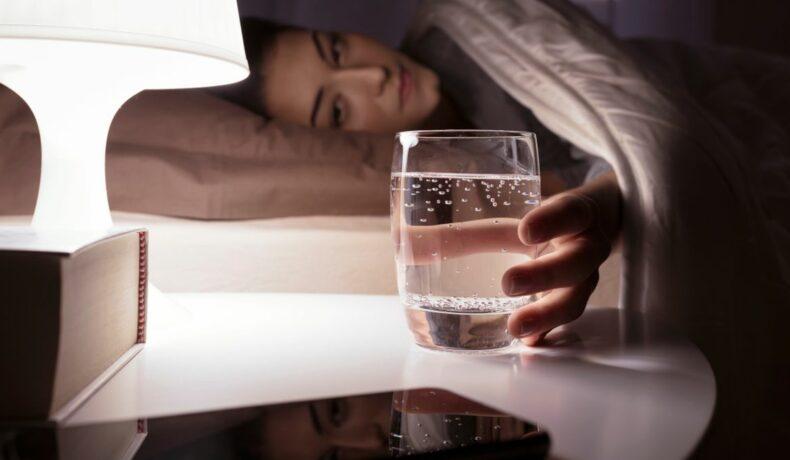 Femeie care stă noaptea în pat și ia un pahar cu apă de pe noptieră. Veioza luminează paharul cu apă și o carte.