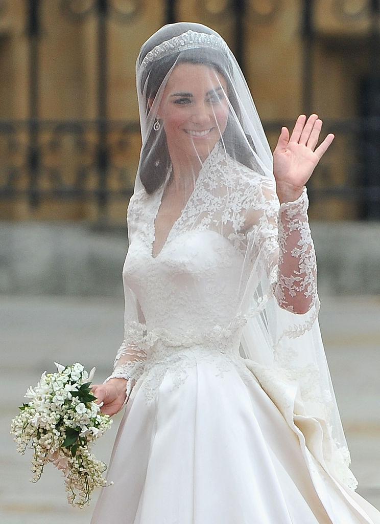 Kate Middleton îmbrăcată în rochie de mireasă și cu voalul pe faț salută mulțimea