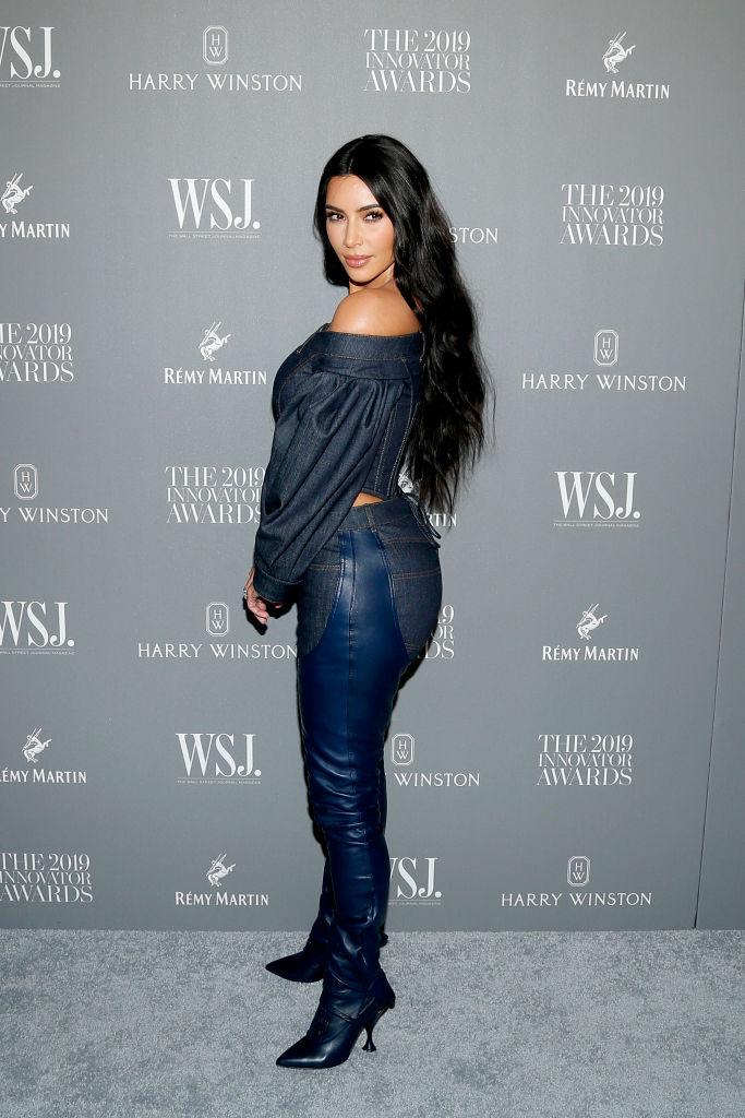 Kim Kardashian îmbrăcată cu o cămașă albasră din denim, blugi și cizme peste genunchi albastre din piele