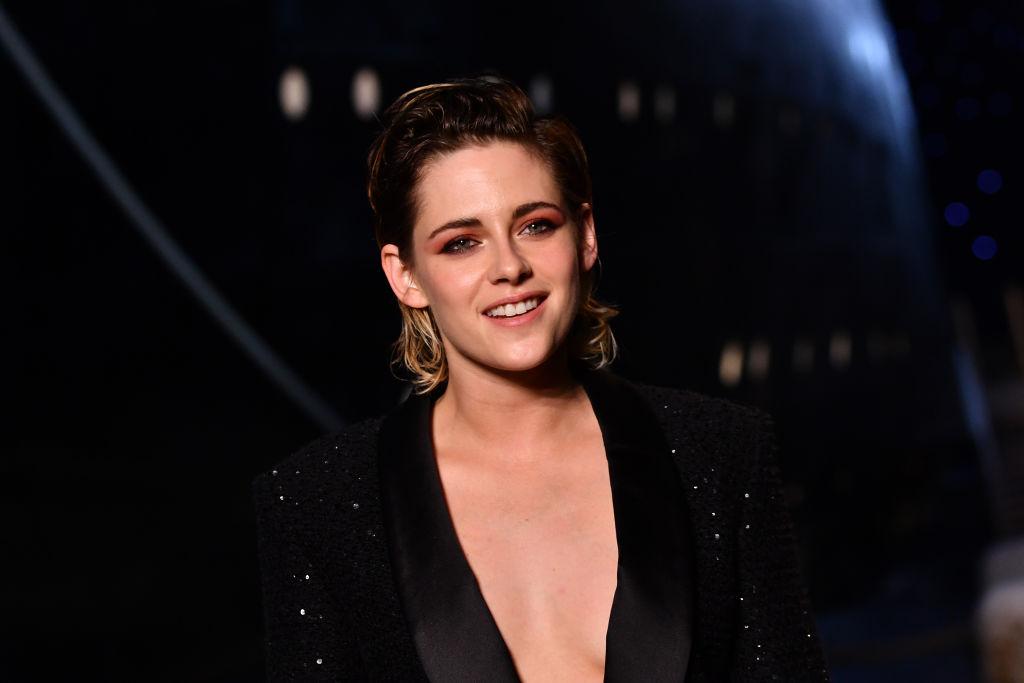 Kristen Stewart îmbrăcată cu un sacou negru decoltat, zâmbind