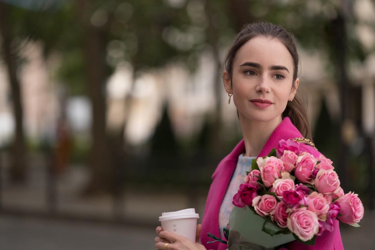 Lilly Collins în timpul filmărilor pentru Emily in Paris îmbrăcată cu un sacou roz și ține în mână un buchet de trandafiri roz