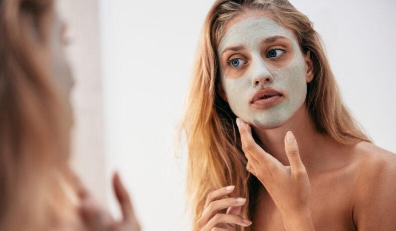 O femeie tânără cu părul lung și blond se uită în oglindă după ce și-a aplicat pe față o mască