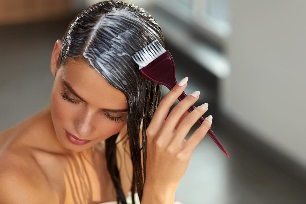 O tânără care aplică una dintre cele mai bune măști naturale pentru păr